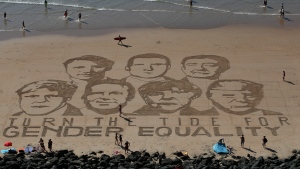 A portrait of G-7 leaders is drawn into the sand over the headline 'Turn the tide for Gender Equality' in Biarritz, France Friday, Aug. 23, 2019. (AP Photo/Peter Dejong)