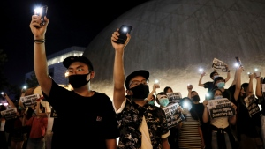 Demonstrators hold their smartphones as they gather at the Hong Kong Space Museum in Hong Kong, Friday, Aug. 23, 2019. Supporters of Hong Kong's pro-democracy movement created human chains on both sides of the city's harbor Friday, inspired by a historic protest 30 years ago in the Baltic states against Soviet control. (AP Photo/Vincent Yu)