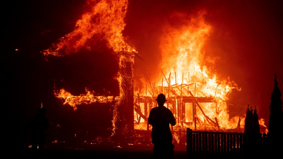 In this Nov. 8, 2018, file photo, a home burns during a wildfire in Paradise, Calif. Paradise High School, in the Northern California town that was mostly destroyed by a wildfire in November 2018, was scheduled to play its first football game Friday, Aug. 23, 2019. (AP Photo/Noah Berger, File)