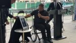 "Rick Hansen unveils a plaque commemorating Mosaic stadium's ""Accessibility Certified Gold"" rating."