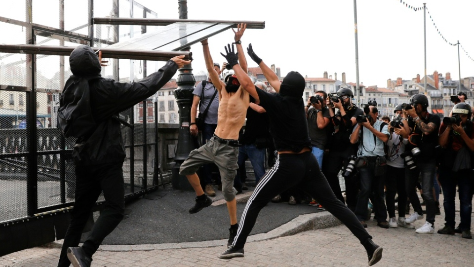 Protesters tear down a part of a G7 barricade put up by French police in Bayonne.
