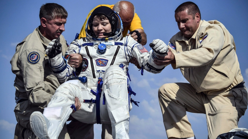 Russian space agency rescue team help U.S. astronaut Anne McClain out of the capsule shortly after the landing of the Russian Soyuz MS-11 space capsule about 150 km south-east of the Kazakh town of Zhezkazgan, Kazakhstan, Tuesday, June 25, 2019. (Alexander Nemenov/Pool Photo via AP)