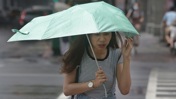 A woman struggles against powerful gusts of wind generated by typhoon Ineng in Taipei, Taiwan, Saturday, Aug. 24, 2019. (AP Photo/Chiang Ying-ying)