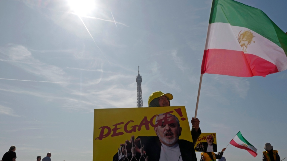 Demonstrators of the National Council of Resistance of Iran demonstrate on the Trocadero square Friday, Aug. 23, 2019 in Paris as Iranian Foreign Minister Javad Zarif is in France. Poster reads: get out. (AP Photo/Michel Spingler)