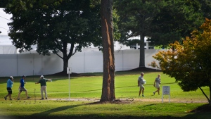 A pine tree is stripped of bark after being struck by lightning on the course at East Lake Golf Club during the third round of the Tour Championship golf tournament Saturday, Aug. 24, 2019, in Atlanta. Several people were injured by the strike. (AP Photo/John Amis)