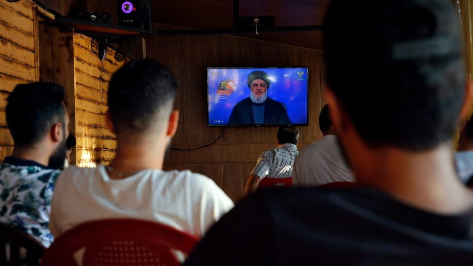 People listen to a speech by Hezbollah leader Sayyed Hassan Nasrallah being broadcast on Hezbollah's al-Manar TV channel, at a coffee shop in a southern suburb of Beirut, Lebanon, Sunday Aug. 25, 2019. (AP Photo/Bilal Hussein)