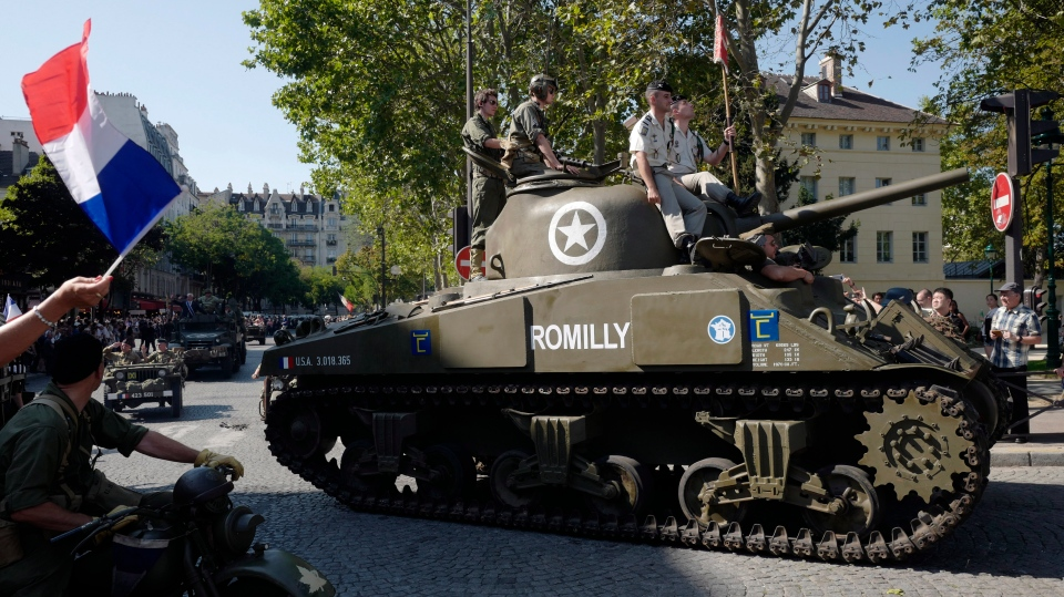 People dressed in World War II era clothes during celebrations of the liberation of Paris from Nazi occupation exactly 75 years ago, in Paris, Sunday, Aug. 25, 2019. (AP Photo/Michel Spingler)