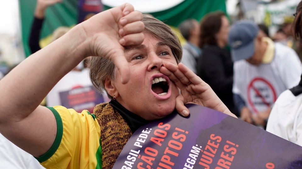 A woman shouts slogans against corruption during a rally in support of the government's