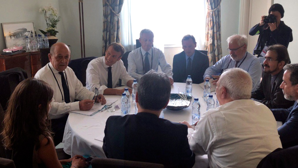 In this photo taken from the Twitter account of Iranian Foreign Minister Mohammad Javad Zarif, shows French President Emmanuel Macron, third left, French Foreign Minister Jean-Yves le Drian, second left, meeting Iranian Foreign Minister Mohammad Javad Zarif, bottom right in white shirt, Sunday, Aug.25, 2019 in Biarritz, southwestern France. (Twitter account of Iranian Foreign Minister Mohammad Javad Zarif via AP)