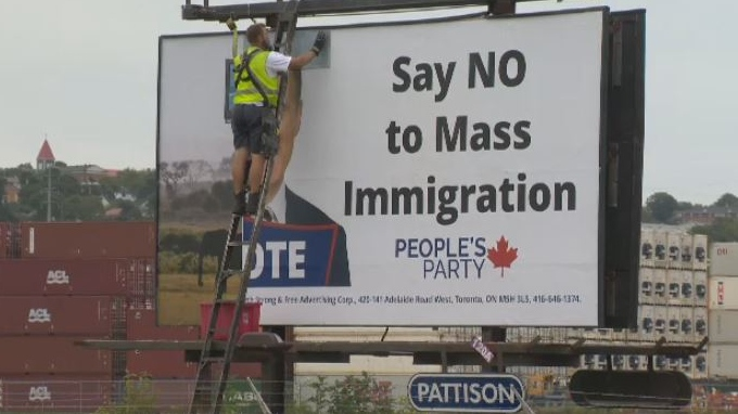 A worker covers over a controversial billboard in Halifax on Aug. 26, 2019. The billboard promoted People's Party of Canada Leader Maxime Bernier's controversial stance on immigration.