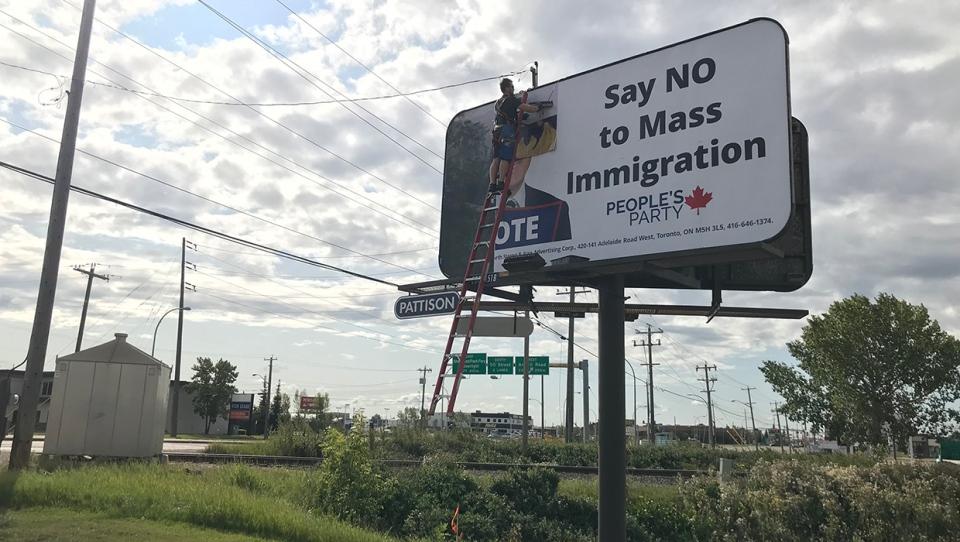A worker removes a Maxime Bernier billboard in Edmonton