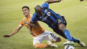 Houston Dynamo's Memo Rodriguez (8) challenges Montreal Impact's Rod Fanni during second half MLS soccer action in Montreal, Saturday, June 2, 2018. THE CANADIAN PRESS/Graham Hughes