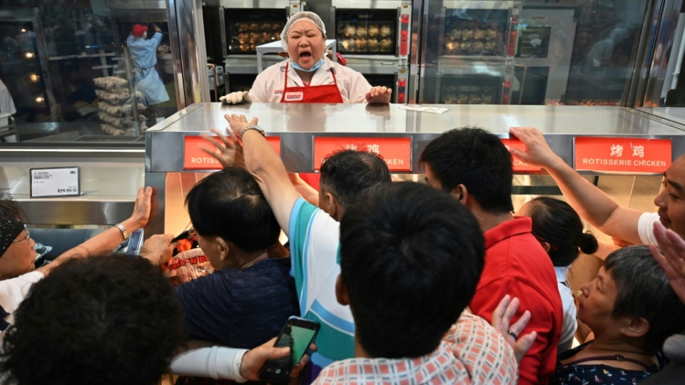 Bargain-hunters battled to get their hands on freshly cooked rotisserie chickens while staff pleaded with them to form a queue. (AFP)