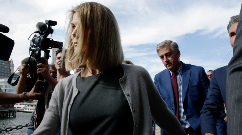 Lori Loughlin departs federal court Tuesday, Aug. 27, 2019, in Boston, after a hearing in a nationwide college admissions bribery scandal. At far right is her husband, clothing designer Mossimo Giannulli. (AP Photo/Steven Senne)