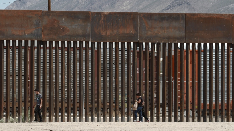 FILE - In this July 17, 2019, file photo, three migrants walk along a border wall set back from the geographical border, in El Paso, Texas, as seen from Ciudad Juarez, Mexico. (AP Photo/Christian Chavez, File)