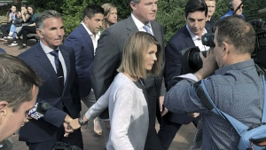 Lori Loughlin depart federal court with her husband, clothing designer Mossimo Giannulli, left, on Tuesday, Aug. 27, 2019, in Boston, after a hearing in a nationwide college admissions bribery scandal. (AP Photo/Philip Marcelo)
