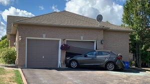 Car smashed into garage in alleged impaired driving incident overnight on Wed., Aug. 28, 2019 (CTV News/Craig Momney)