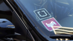 A ride share car displays Lyft and Uber stickers on its front windshield in downtown Los Angeles on Jan. 12, 2016. (AP / Richard Vogel)