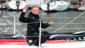 Greta Thunberg, a 16-year-old Swedish climate activist, waves after sailing in New York harbor aboard the Malizia II, Wednesday, Aug. 28, 2019. (AP Photo/Mary Altaffer)