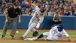 Toronto Blue Jays' Randall Grichuk safe at third base on a passed ball to the plate as Atlanta Braves' Josh Donaldson tries to handle throw from his catcher in the fifth inning of their Interleague MLB baseball game in Toronto Wednesday August 28, 2019. THE CANADIAN PRESS/Fred Thornhill