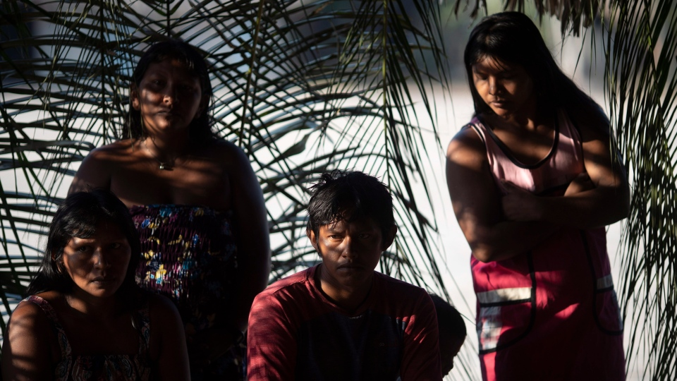 In this Aug. 27, 2019 photo, members of the Kayapo indigenous group attend a meeting to discuss community issues in their village Bau, located on Kayapo indigenous territory in Altamira in Brazil's Amazon. (AP Photo/Leo Correa)