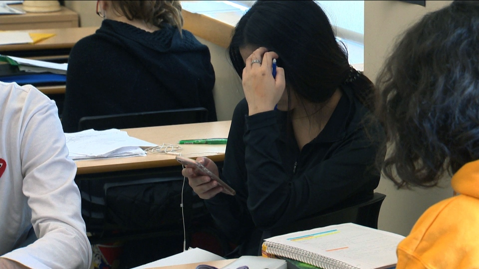 A student is seen using their cellphone inside a classroom in this undated image. (CTV News Toronto)