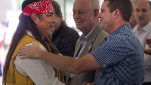 Mohawk Grand Chief Serge Simon, left, shakes hands with Oka Mayor Pascal Quevillon after ceremonies marking the 25th anniversary of the Oka crisis Saturday, July 11, 2015 in Kanesatake, Que. A Mohawk grand chief and the mayor of Oka, Que., stood side-by-side today for the first time since tensions erupted in July over a centuries' old land dispute between the two communities. THE CANADIAN PRESS/Ryan Remiorz