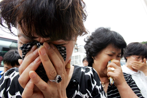 Relatives of South Koreans kidnapped in Afghanistan weep near the U.S. Embassy in Seoul, South Korea on Wednesday, Aug. 1, 2007. (AP / Ahn Young-joon)