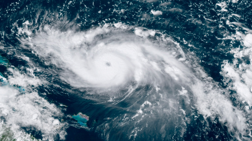 This GOES-16 satellite image taken Friday, Aug. 30, 2019, at 17:30 UTC and provided by National Oceanic and Atmospheric Administration (NOAA), shows Hurricane Dorian, right, moving over open waters in the Atlantic Ocean.  (NOAA via AP)