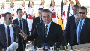 In this handout photo released by the government news agency Agencia Brasil, Brazil's President Jair Bolsonaro, center, talks with the reporters outside the presidential official residence Alvorada Palace, in Brasilia, Brazil, Tuesday, Aug. 27, 2019. (Antonio Cruz/Agencia Brasil via AP)