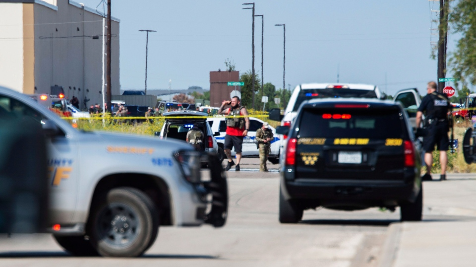 """Odessa and Midland police and sheriff's deputies surround the area behind Cinergy in Odessa, Texas, Saturday, Aug. 31, 2019, after reports of shootings. Police said there are """"multiple gunshot victims"""" in West Texas after reports of gunfire on Saturday in the area of Midland and Odessa. (Tim Fischer/Midland Reporter-Telegram via AP)"""
