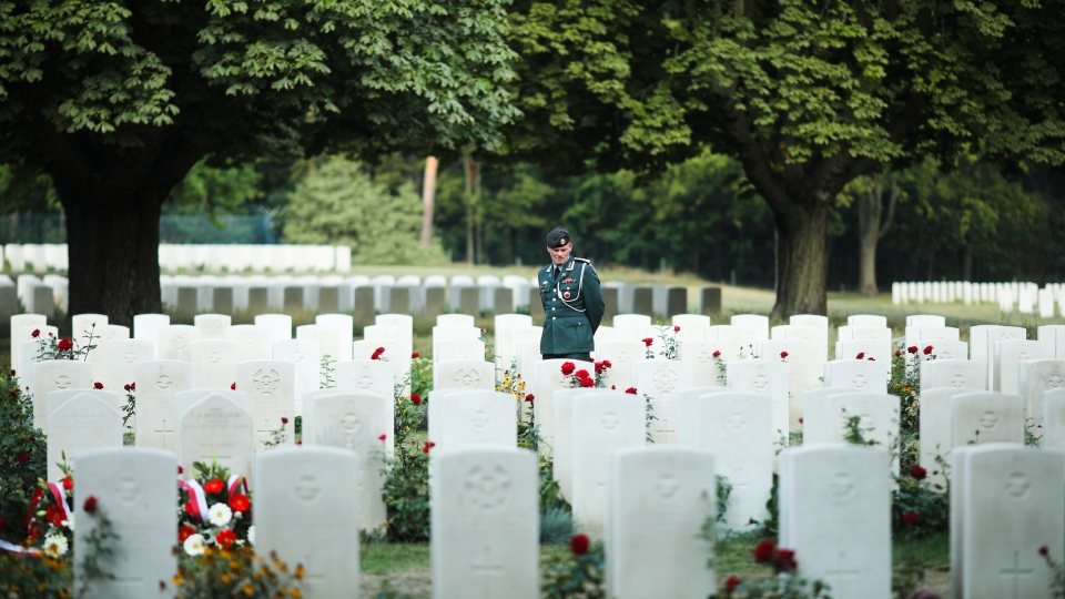 A soldier walks between graves of soldiers prior to a wreath laying ceremony to commemorate the Nazi-German invasion of Poland and the beginning of WWII, 80-years ago, at the British War Cemetery in Berlin, Germany, Sunday, Sept. 1, 2019. (AP Photo/Markus Schreiber)