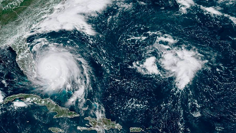 This GOES-16 satellite image taken Monday, Sept. 2, 2019, at 16:40 UTC and provided by National Oceanic and Atmospheric Administration (NOAA), shows Hurricane Dorian, left, churning over Bahamas. (NOAA via AP)