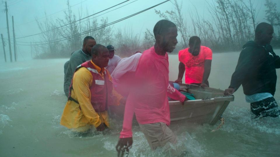 Volunteers rescue several families from the rising waters of Hurricane Dorian, near the Causarina bridge in Freeport, Grand Bahama, Bahamas, Tuesday, Sept. 3, 2019. (AP Photo/Ramon Espinosa)