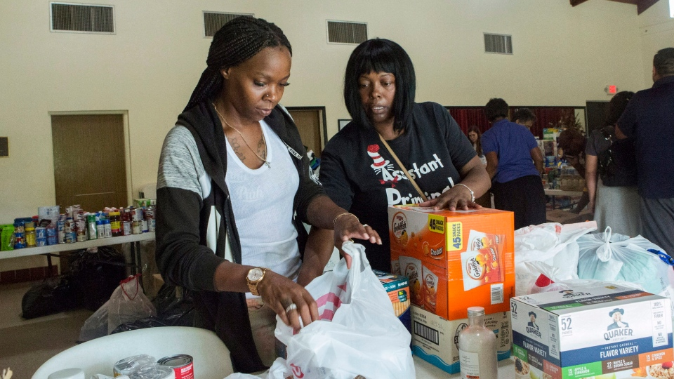 Volunteers Jazz Williams, 29, left, and Jodye Scavella, 47, organize donated goods for those affected by Hurricane Dorian in the Bahamas, at Christ Episcopal Church in Miami, Tuesday, Sept. 3, 2019. (AP Photo/Ellis Rua)