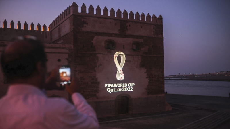 A man takes a photo of the landmark Kasbah of Oudayas as it is illuminated by the emblem of Qatar World Cup 2022, in Rabat, Morocco, on Sept. 3, 2019. (Mosa'ab Elshamy / AP)