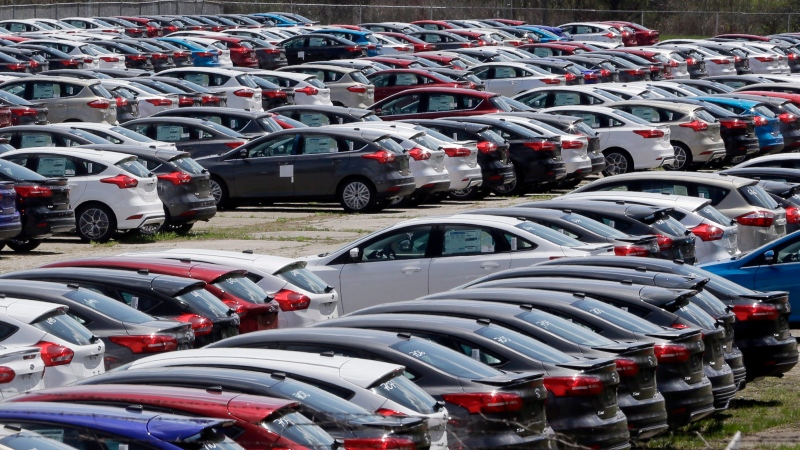 In this May 1, 2015, file photo Ford Focus vehicles are seen on a storage lot in Ypsilanti, Mich. By the 2025 model year, nearly all new vehicles sold in the U.S. will come with electronic alerts to prompt people to check the backseat for their children. (AP Photo/Carlos Osorio, File)