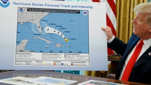 U.S. President Donald Trump holds a chart as he talks with reporters after receiving a briefing on Hurricane Dorian in the Oval Office of the White House, Wednesday, Sept. 4, 2019, in Washington. (AP Photo/Evan Vucci)