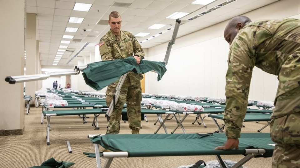 U.S. Army National Guard Pvt. Christopher Zambuto, left, and Specialist Jermaris Hamilton assemble cots in a shelter for Hurricane Dorian evacuees inside the old Sears location at Northgate Mall, on Wednesday, Sep. 4, 2019, in Durham, NC. (Casey Toth/The News & Observer via AP)