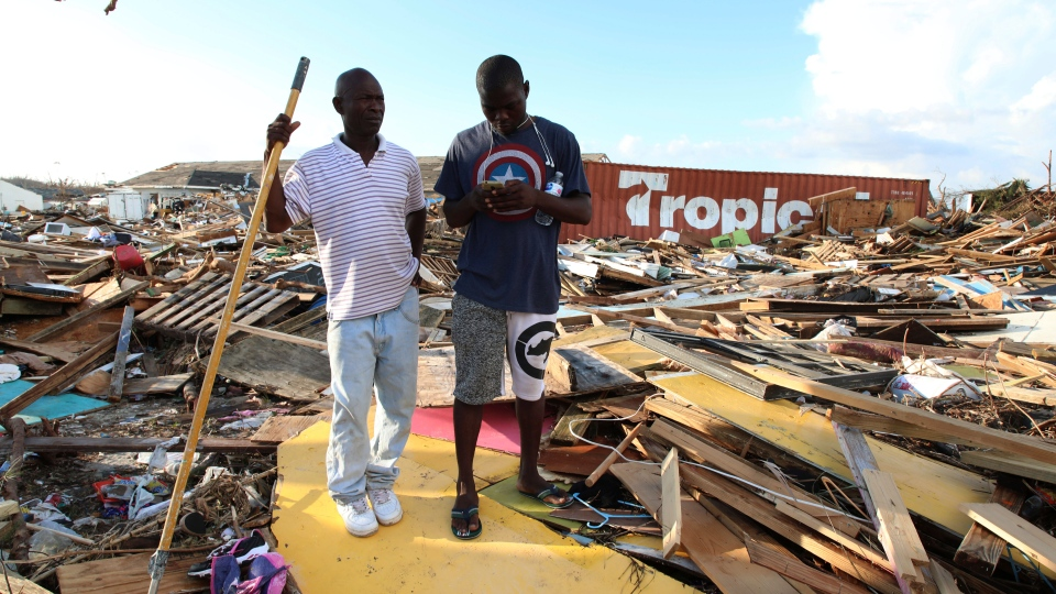 Haitian Burris Filburt, right, and another man stand on the extensive damage and destruction in the aftermath of Hurricane Dorian is seen in The Mudd, Great Abaco, Bahamas, Thursday, Sept. 5, 2019. (AP Photo/Gonzalo Gaudenzi)