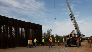 In this Aug. 23, 2019 file photo, workers break ground on new border wall construction about 20 miles west of Santa Teresa, N.M. Construction on a Pentagon-funded portion of the border wall began near Yuma, Arizona, this week, just as federal authorities announced they are diverting even more defense funds for wall projects. Crews began constructing a 30-foot steel fence along the Colorado River this week. (AP Photo/Cedar Attanasio, File)