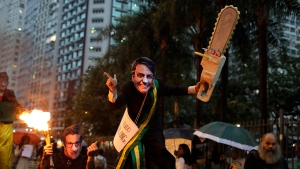 A demonstrator wearing a Brazilian President Jair Bolsonaro mask and brandishing a fake chainsaw, center, with another wearing a mask o Brazil's Environment Minister Ricardo Salles, march in defense of the Amazon in Rio de Janeiro, Brazil, Thursday, Sept. 5, 2019. (AP Photo/Silvia Izquierdo)