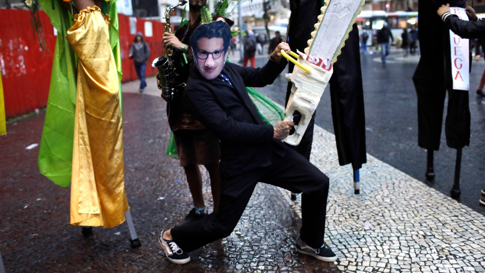 A demonstrator wearing a mask with the likeness of Brazil's Environment Minister Ricardo Salles brandishing a fake chainsaw, participates in a protest to defend of the Amazon, in Rio de Janeiro, Brazil, Thursday, Sept. 5, 2019. (AP Photo/Silvia Izquierdo)