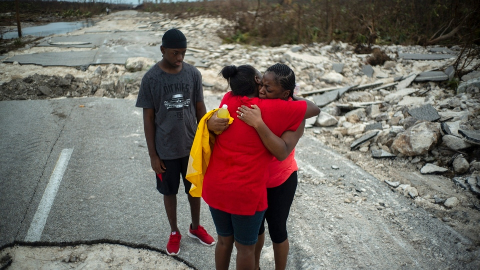 Brennamae Cooper, right, cries and hugs a friend after finding themselves walking in opposite directions, one escaping the destruction of Hurricane Dorian and the other on the way to search for her relatives, on a shattered road near the town of High Rock, Grand Bahama, Bahamas, Thursday Sept. 5, 2019. (AP Photo / Ramon Espinosa)