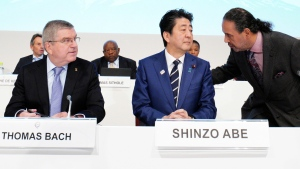 FILE - In this Nov. 28, 2018, file photo, Japanese Prime Minister Shinzo Abe, center, and IOC President Thomas Bach, left, listen to Sheikh Ahmad al Fahad al Sabah, president of the Association of National Olympic Committees (ANOC), during the opening of the ANOC general assembly in Tokyo. (AP Photo/Eugene Hoshiko, File)