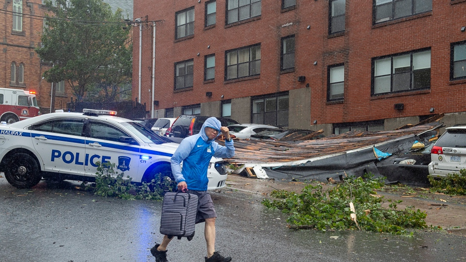 An unidentified man heads past part of an apartment roof that landed on several cars in Halifax as hurricane Dorian approaches on Saturday, Sept. 7, 2019. Residents were evacuated from the building. THE CANADIAN PRESS/Andrew Vaughan