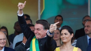 In this photo released by Brazil's Presidential press office, Brazil's President Jair Bolsonaro attends an Independence Day military parade accompanied by first lady Michelle Bolsonaro, in Brasilia, Brazil, Saturday, Sept. 7, 2019. Bolsonaro has overseen Brazil's independence day celebrations with a renewed assertion of his country's sovereignty over the Amazon. (Marcos Correa/Brazil's Presidential Press Office via AP)