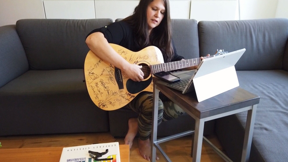 Joni Delaurier works on her song for the Acoustic Guitar Project on a guitar festooned with signatures. (CTV News Calgary)