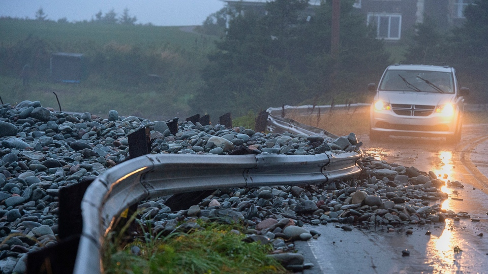 A guard rail was damaged by powerful waves that drove rocks on shore in Cow Bay, N.S. on Saturday, Sept. 7, 2019. Hurricane Dorian brought wind, rain and heavy seas that knocked out power across the region and left damage to buildings and trees. THE CANADIAN PRESS/Andrew Vaughan