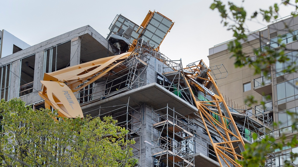 A toppled building crane is draped over a new construction project in Halifax on Sunday, Sept. 8, 2019.  (THE CANADIAN PRESS/Andrew Vaughan)